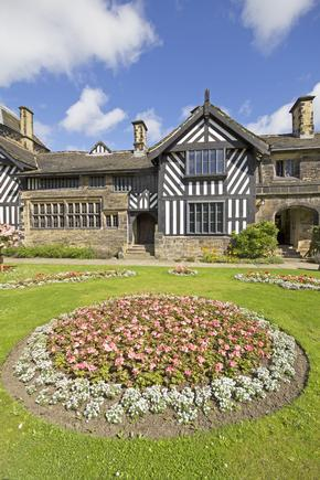 Shibden Hall near Halifax on a sunny day with flower beds in foreground