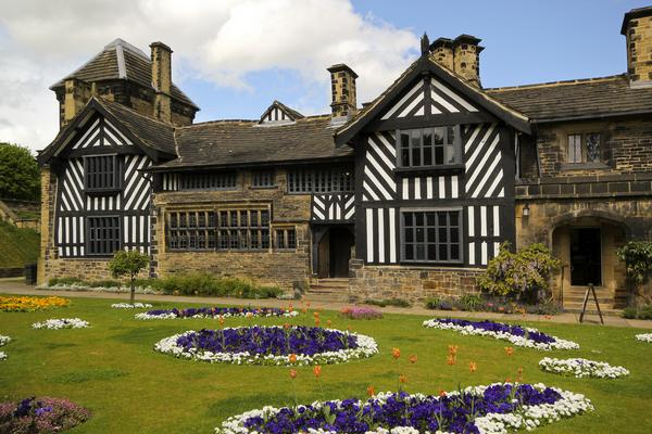 View of exterior of half-timbered Shibden Hall, with decorative flower beds in foreground