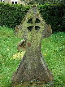 A headstone in the churchyard of St. John the Evangelist church. © Lizz Mollington