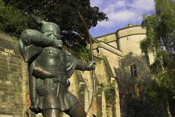 Statue of Robin Hood flexing his bow, with Nottingham Castle in background